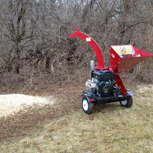 Wood chips spraying out of merry commercial wood chipper